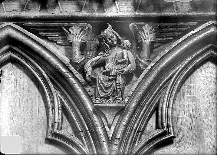 Cathédrale Saint-Pierre Stalles, écoinçon : ange proteur de couronnes et figure symbolique des Péchés capitaux, Heuzé, Henri (photographe),